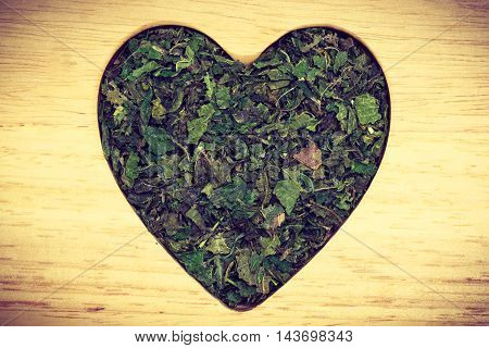Healthy food healing herbs alternative herbal medicine concept. Dried herb nettle leaves in form of heart on wooden board