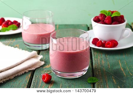 Healthy berry with raspberry, oatmeal and mint in a glass, on wooden table