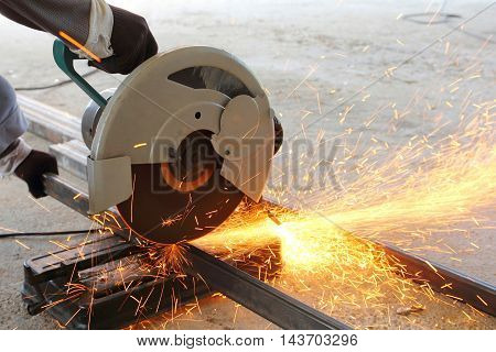 Worker use grinding machine cutting a steel