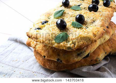 Stack of traditional Italian bread focaccia on the linen napkin. Homemade traditional Italian bread focaccia.