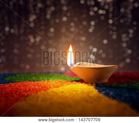 Traditional diya lamp lit on colorful rangoli