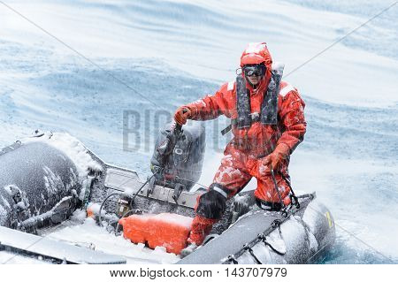 SOUTH GEORGIA, GREAT BRITAIN - NOV 9, 2012:  Unidentified man in a water proof suite in a rubber boat with a motor in the Atlantic Ocean. Atlantic Ocean is the world's second largest ocean