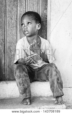 KARA, TOGO - MAR 9, 2013: Unidentified Togolese boy sits at the porch of a house. Children in Togo suffer of poverty due to the unstable econimic situation