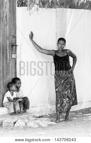 KARA, TOGO - MAR 9, 2013: Unidentified Togolese children sit near a house door. Children in Togo suffer of poverty due to the unstable econimic situation