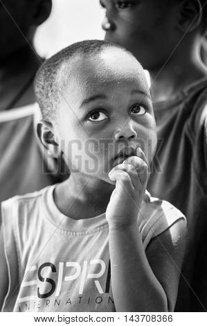KARA, TOGO - MAR 9, 2013: Unidentified Togolese boy thinks of something. Children in Togo suffer of poverty due to the unstable econimic situation