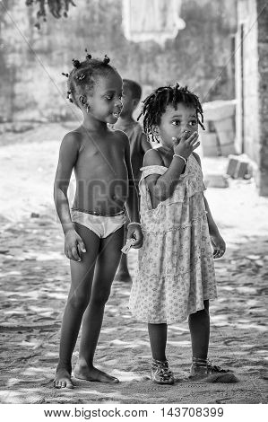 KARA, TOGO - MAR 9, 2013: Unidentified Togolese girls walk in the street. Children in Togo suffer of poverty due to the unstable econimic situation