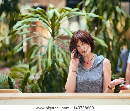 Portrait of woman sitting at cafe and using her smartphone