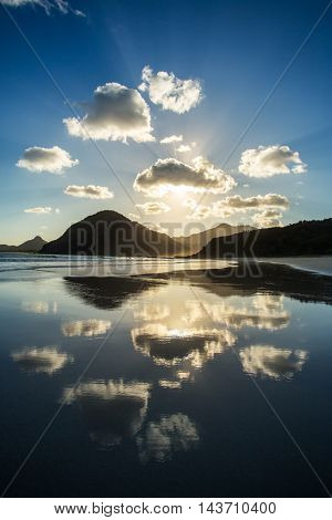 Beautiful ocean sunset. Clouds and sun light reflecting in the water on the beach