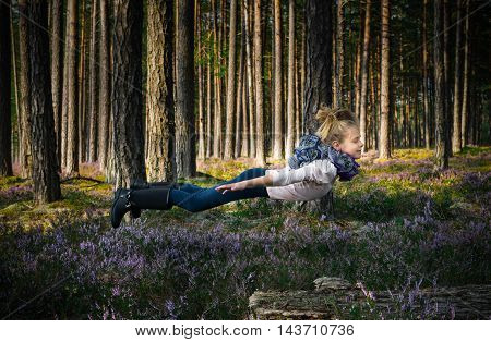 Beautiful blond girl levitates in the forest. Fairy tale