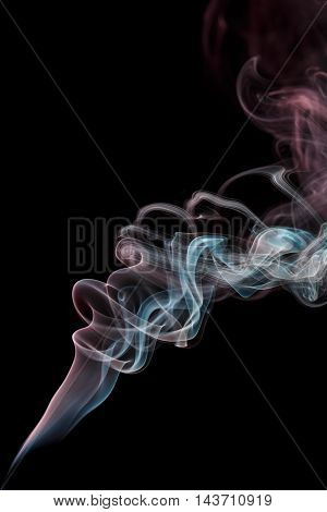 Abstract art. Color smoke from the aromatic sticks on a black background. Background for Halloween. Texture fog. Design element. The concept of aromatherapy.