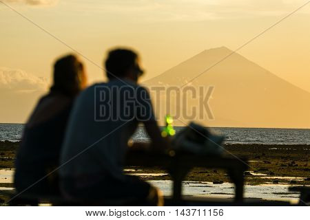 Tourists in the restaurant on Gili Travangan island enjoying evening sunset view on Gunung Batur volcano on Bali, Indonesia.