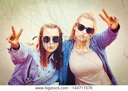 Two pretty girls friends doing peace sign