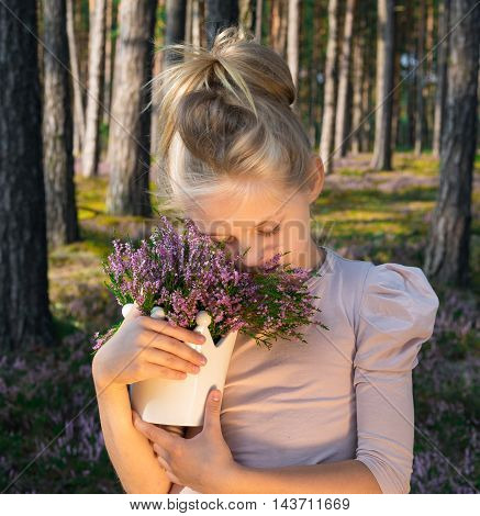 Beautiful girl in the forest holding in a vase with heather. Forest.
