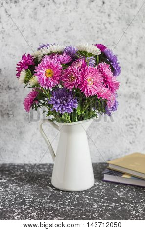 Bouquet of autumn flowers asters and a stack of books on a gray table. Home still life in vintage style