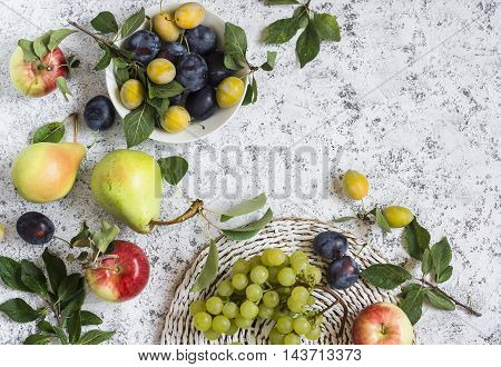 Assortment of fresh summer fruit - grapes pears apples plums on a light background top view. Free space for text