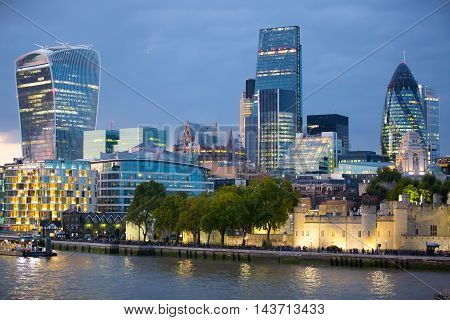 LONDON, UK - SEPTEMBER 19, 2015: City of London with first night lights at sunset. Modern business and banking aria. View from the Tower bridge include Walkie-Talkie and Gherkin building