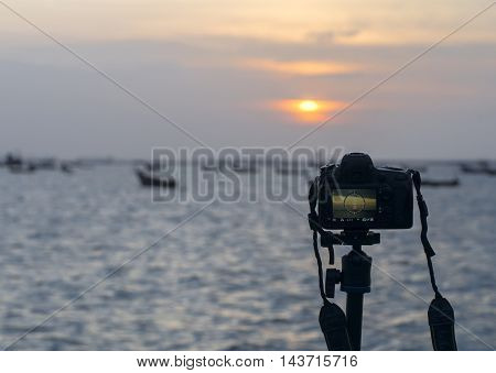Closeup of a camera on a tripod outdoors. Background Landscape out of focus