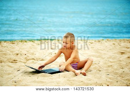 boy sitting with a laptop on the beach . Computer addiction .