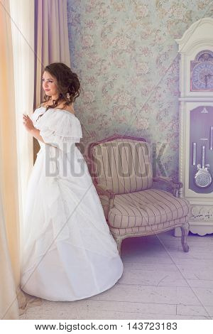 Pretty adult woman wearing vintage beautiful white dress standing in bright retro room and looking out the window