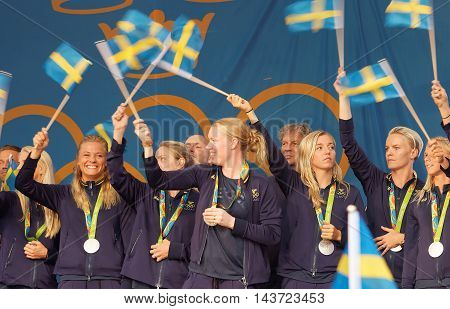 STOCKHOLM SWEDEN - AUG 21 2016: Happy swedish female soccer team waving swedish flags when the swedish olympic athletes are celebrated in Kungstradgarden StockholmSwedenAugust 212016