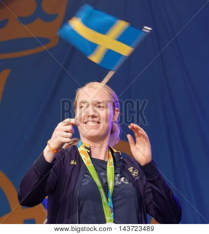 STOCKHOLM SWEDEN - AUG 21 2016: Swedish female soccer keeper Hedvig Lindahl waiving the swedish flag when the swedish olympic athletes are celebrated in Kungstradgarden StockholmSwedenAugust 212016
