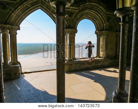 MONT SAINT-MICHEL, FRANCE - MAY 04, 2014: The little girl looks at the bay from windows of Mont Saint-Michel Abbey, France