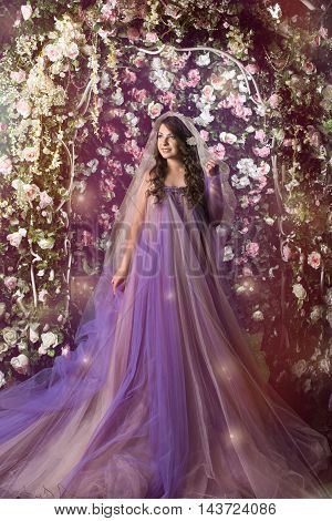 Beautiful woman standing in violet long dress under arch of pink and white roses