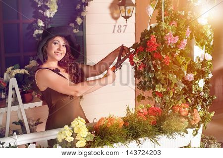Pretty smiling brunette woman cutting plants with secateurs in garden