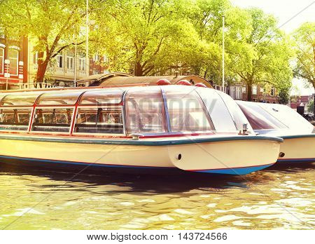 Tour boats or cruise ships in the sun. Amsterdam sightseeing boats or passenger ships.