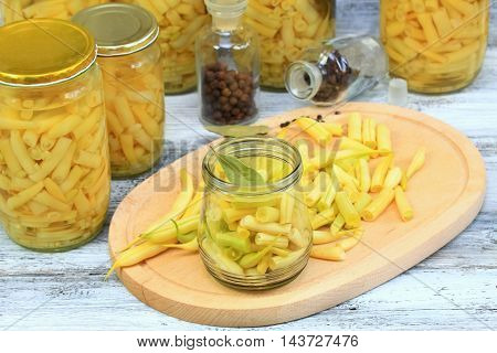 Homemade preserved yellow beans in spicy pickle cut beans with bay leaf in the jar at the front