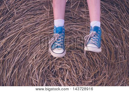 Baby feet shod in old blue sneakers