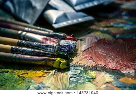 Old palette, oil paint and art brushes