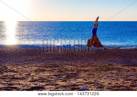 An attractive young woman doing a yoga pose for balance and stretching staying on seafront beach at colorful Sunrise