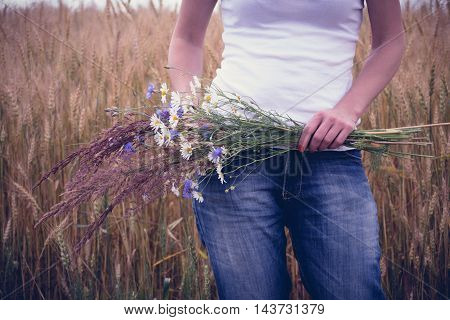 Woman with a bouquet of flowers in a field