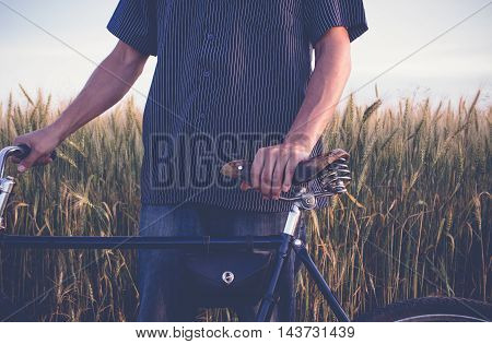 Mature man standing with retro bike in the field