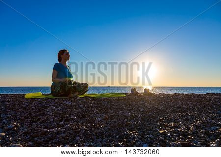 Young Woman meditating on rocky Ocean Beach sitting on green Yoga Mat sporty Shoes staying apart luminous Sunrise with reflections in Sea Surf blue Sky
