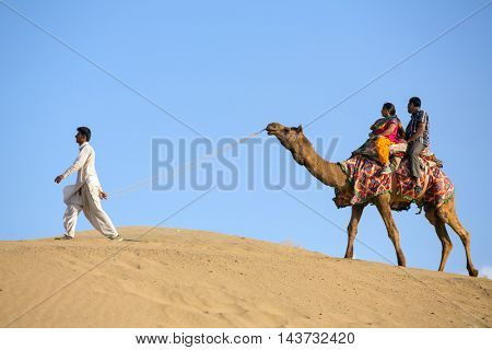 Jaisalmer, India - March 13, 2016: Indian tourists on the camel in Thar desert, Rajasthan, India