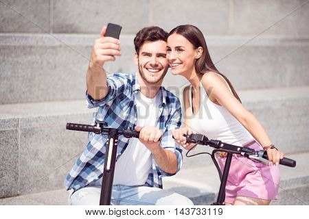 Just smile. Cheerful content smiling friends making selfies and holding scooters while resting together