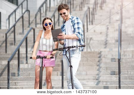 Active way of life. Cheerful delighted smiling friends using tablet and expressing joy while standing near scooters