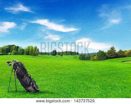 Idyllic golf course with golf bag and green meadow.