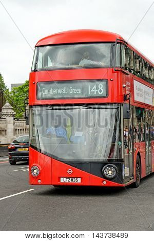 LONDON UK - JULY 8 2016: People ride New Routemaster bus near Parliament square. The hybrid diesel-electric bus is a new modern version of iconic double decker and 50 % more fuel efficient.