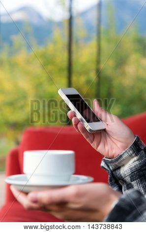 Person holding white Coffee Mug and Telephone at Hotel Lobby with green Forest on background outside large Windows