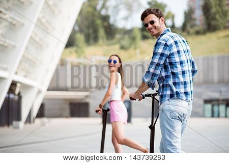 Emotionally charged. Positive content smiling friends expressing joy and riding kick scooters while resting together