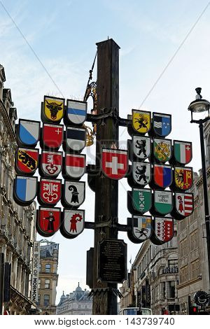 LONDON ENGLAND - JULY 8 2016: View of Swiss Cantonal Tree (erected 1991) on Leicester Square. This Cantonal Tree displays coats of arms of twenty-six cantons of Switzerland.