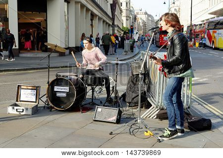 LONDON ENGLAND - JULY 8 2016: Street musicians perform in front of the Charing Cross Station. Dozens buskers perform on the streets of London.