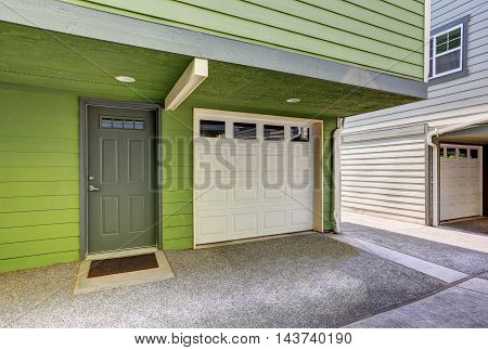 Small entrance porch and garage door of green duplex house. Northwest USA poster