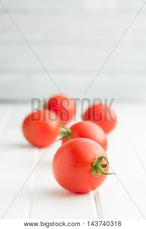 Fresh tomatoes on white table.
