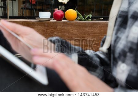 Hands of Person browsing tablet PC screen close up with Coffee Mug and Pomegranate and Orange on foreground, focus on fruits and white coffee Cup
