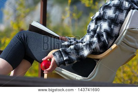 Serene Scene Person sitting in Chair inside rural Garden reading Book holding Pomegranate casual Clothing Daylight