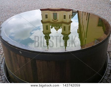 Reflection Of A Church In A Wooden Barrel Full Of Water